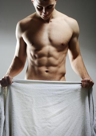 nackte brust: Ein nackter junger Mann deckte sich mit einem Handtuch als Kopie Raum