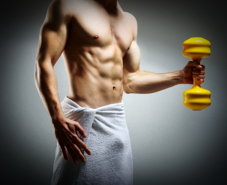 Modybuilder doing heavy weight exercise with dumbbells against dark background Stock Photo