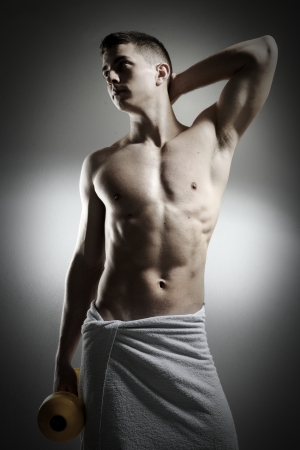Male with towel holding dumbbell photo