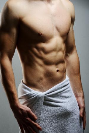Mladý macho muž pomocí bílý ručník