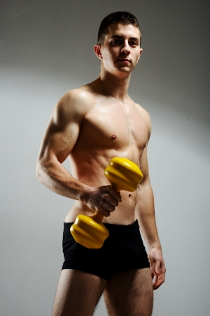Modybuilder doing heavy weight exercise with dumbbells against dark background photo