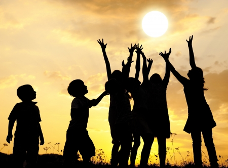 Group of happy children catching sun with their arms Stock Photo
