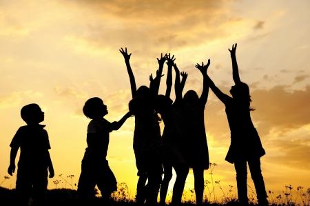 silueta niño: Silueta, grupo de ni?felices jugando en la pradera, puesta del sol, verano