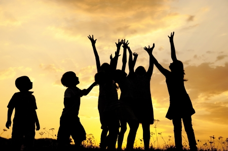 Group of children silhouettes playing on nature field at sunset summertime photo