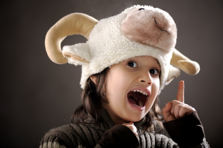 Portrait of authentic cute kid wearing funny sheep hat photo