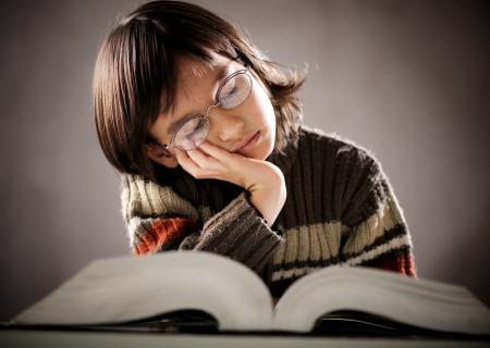 Fine portrait of cute little student kid falling asleep photo