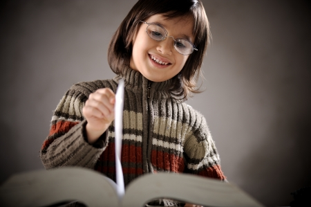 Fine portrait of cute little boy reading book page photo