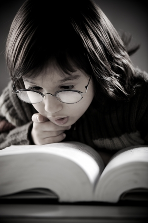 Retro portrait of cute little boy reading book Stock Photo