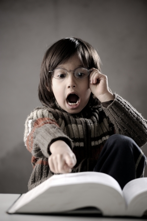 Fine portrait of cute little boy reading book photo