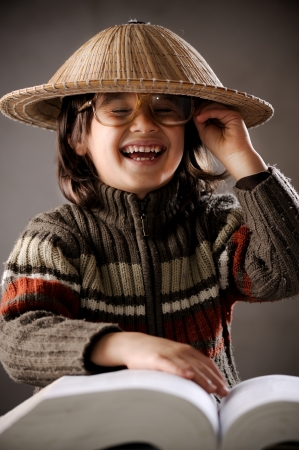 Closeup portrait of cute kid wearing chinese hat reading book photo