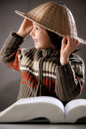 chinese hat: Closeup portrait of cute kid wearing chinese hat reading book