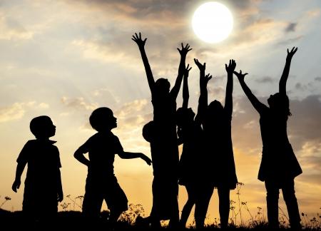 kind silhouet: Silhouette, de groep van gelukkige kinderen spelen op de weide, zonsondergang, zomer