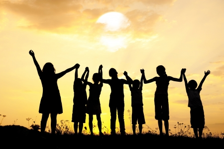 hands in the air: Group of happy children standing on meadow at summer sunset Stock Photo