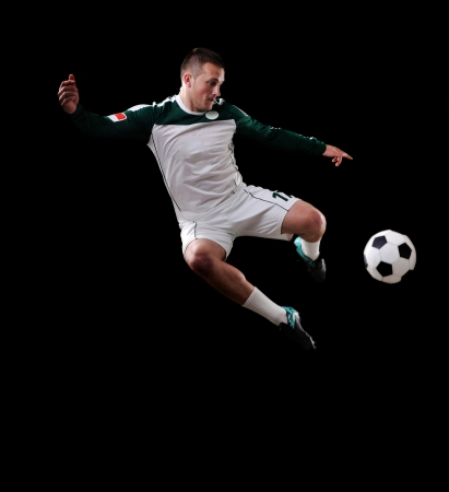 Soccer player in the air over black background Stock Photo