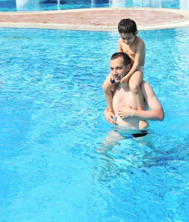 Smiling father and son leaning in the water pool photo