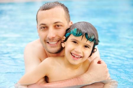 Sourire père et le fils se penchant dans la piscine d'eau