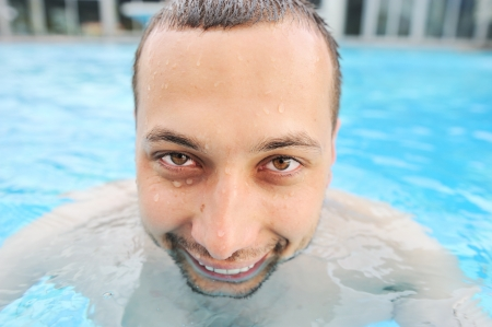 Closeup portrait of a handsome funny and happy young man in pool photo