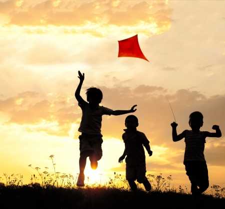 Group of happy children playing with kite on meadow at summertime sunset Standard-Bild
