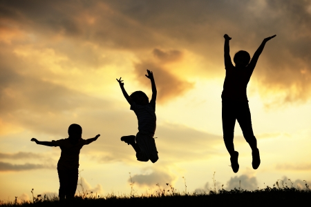 Active group of kids spending happy time on summer sunset at meadow Stock Photo