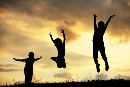 Aktivní skupina dětí tráví šťastné času na letní západ slunce na louce