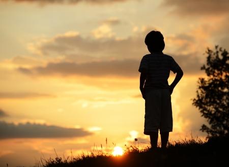 Actieve jongen tijd doorbrengen op zomer weide door zonsondergang
