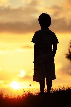 silueta niño: Activo pasar tiempo cabrito en la pradera de verano al atardecer