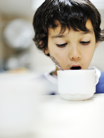 Kid in kitchen drinkin from the cup photo