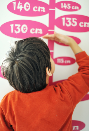 Boy growing tall and measuring his height on the wall Standard-Bild