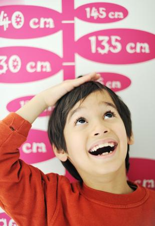 Chlapec rostoucí vysoký a měření jeho výšky na stěnu