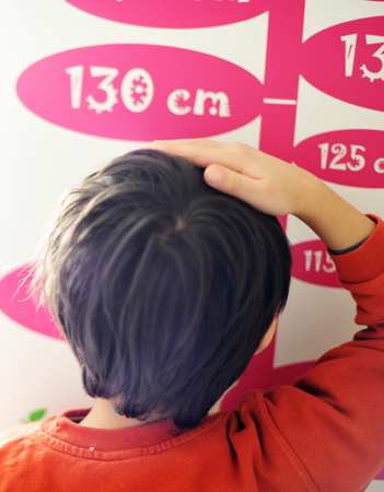 tallness: Cute kid measuring his height Stock Photo