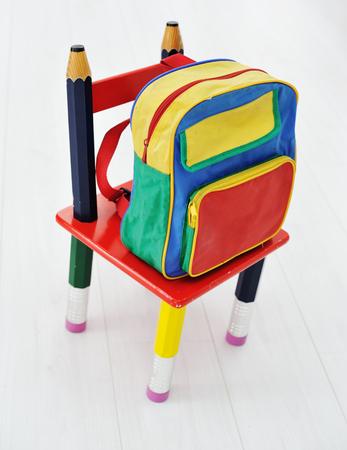 mochila escolar: Morral de la escuela de colores y sillita Foto de archivo