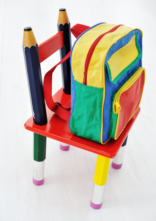 Colorful school backpack and little chair photo
