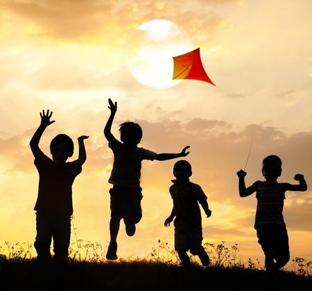 volar: Grupo de niños felices corriendo y jugando con la cometa en prado al atardecer el horario de verano