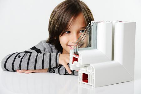 double glazing: Kid holding plastic window profile Stock Photo