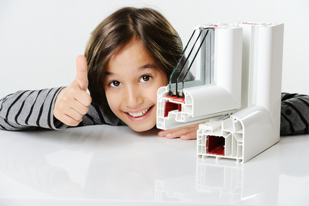 aluminium background: Kid holding plastic pvc window profile Stock Photo