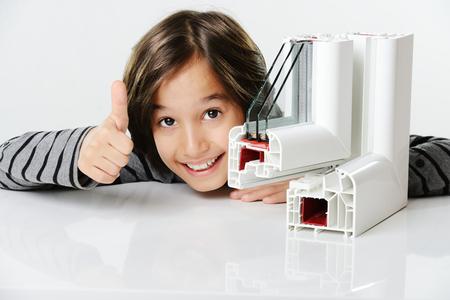 ventana abierta interior: Kid sosteniendo perfil de la ventana del pvc plástico