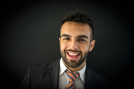succesful: Portrait of attractive man against black smiling