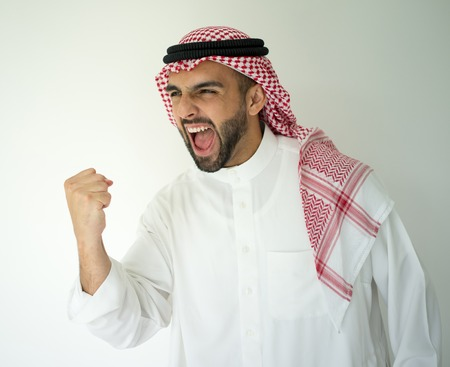 arabic man: Arabic young businessman posing on red wall yelling celebrating