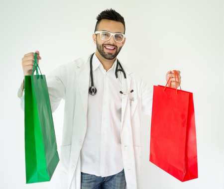 Portrait of attractive doctor with shopping bags for gifts photo
