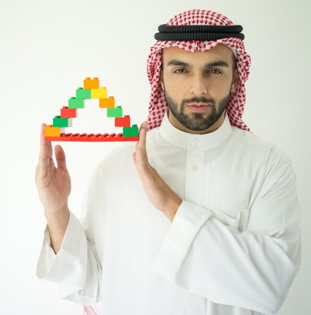 play blocks: Arabic young businessman building cube house