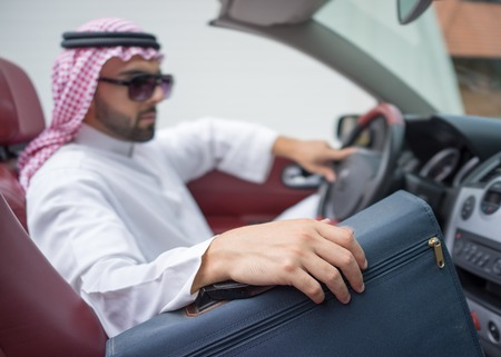 riches adult: Arabic young businessman driving car and holding briefcase Stock Photo