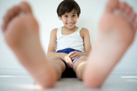 boy underwear: Adorable little happy boy sitting on ground and looking at camera