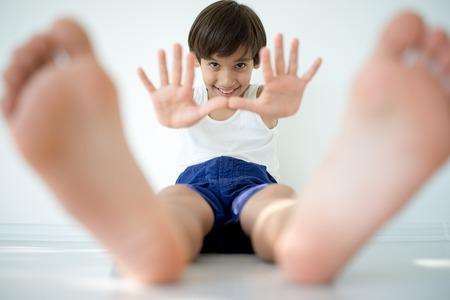 manos y pies: Pequeño muchacho feliz adorable que se sienta en el suelo y mirando a la cámara