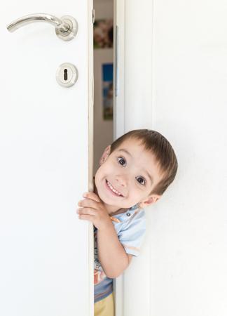 peeking: Kid peeking out of the open room door