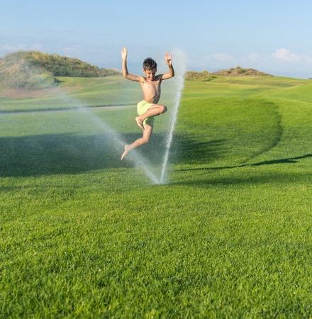 teen golf: Vacaciones de verano feliz para los ni�os en el chapoteo del agua aspersi�n verde prado