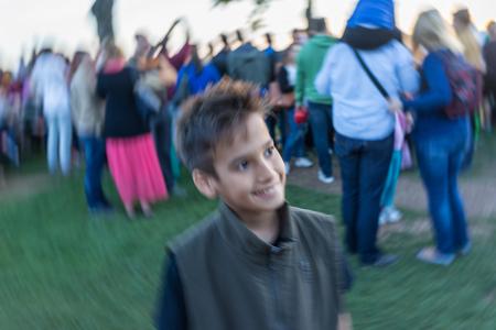 niños sonriendo: Cabrito que se coloca en el grupo de personas con el desenfoque de movimiento circular