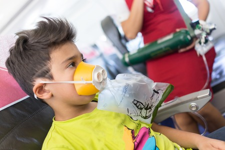 oxigen: Kid traveling by airplane with need for oxigen first emergency aid Stock Photo