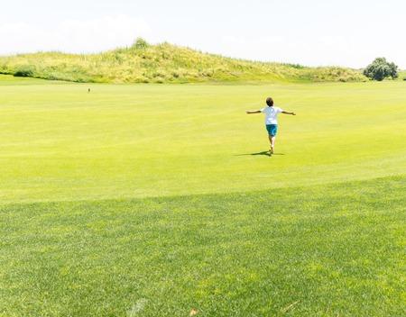 green meadow: Little kid running on green meadow