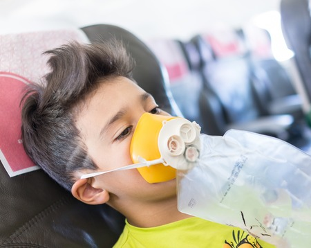 emergency: Kid traveling by airplane with need for oxigen first emergency aid Stock Photo
