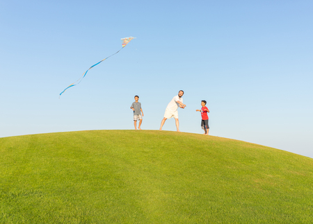 family playing: Running with kite on summer holiday vacation, perfect meadow and sky on seaside
